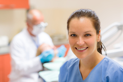 A dental technician smiles outwardly while a dentist works with a patient in the background